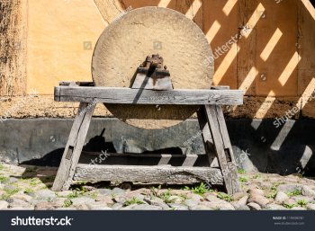 stock-photo-mounted-on-a-wooden-frame-of-an-old-grinding-stone-used-for-sharpening-metal-objec...jpg
